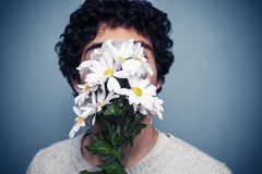 Young man hiding behind flowers. Young multi racial man is hiding behind a small bouquet of flowers Stock Photo
