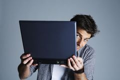 Young man hiding behind laptop computer Stock Images