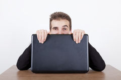 Hiding behind a laptop Royalty Free Stock Image