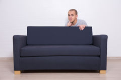 Young man hiding behind a sofa and showing shhh sign Stock Images