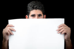 Young man hiding behind a white banner Stock Photography