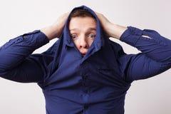 Young man hiding in a blue shirt hiding his face Stock Photos