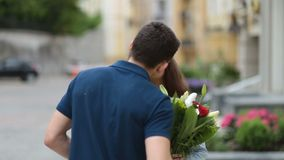 Young man hiding flowers for girl behind his back stock video footage