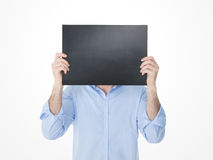 Young man hiding his face behind an empty blackboard Stock Photography