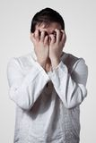 Young man hiding his face with hands Stock Photography