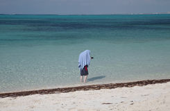 Young man hiding from the sun under a towel. A fair-skinned young man with a camera hiding from the hot sun under a towel that is draped over his head, shoulders Stock Images