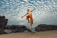 Young man high jumping on beach Royalty Free Stock Photos