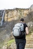 Young Man in a High Mountain looking Big Waterfall stock images