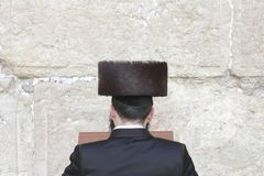 Young man with high, tied hat praying at the Wailing Wall in Jerusalem Royalty Free Stock Photography