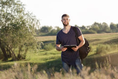 Young man on hike in nature using digital tablet Stock Images