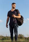 Young man on hike in nature using phone Royalty Free Stock Photos