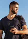 Young man on hike in nature using phone. Portrait Royalty Free Stock Image