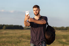 Young man on hike in nature using phone. Portrait Royalty Free Stock Photo