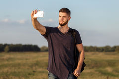 Young man on hike in nature using phone. Portrait Stock Image