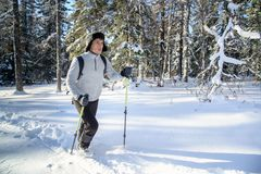 Young Man hiker with backpack trekking in winter snowy forest . Winter leisure, sports and activity. Young Man hiker with backpack trekking in winter snowy Stock Photo