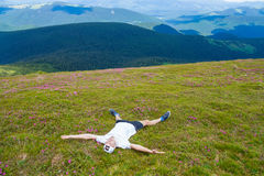 Young man hiker lies on the top of hill and admiring beautiful mountain valley view Royalty Free Stock Photo