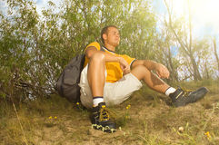Young man hiker relaxing on the hill. On sunny day royalty free stock photography