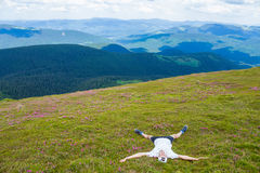 Young man hiker relaxing on the top of hill and admiring beautiful mountain valley view Stock Photos