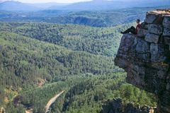 Young man hiker sitting on top of a mountain on on high altitude and getting inspired by amazing view. - Wide shoot with. Young man hiker sitting on top of a royalty free stock image