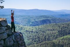 Young man hiker standing on top of a mountain with raised up hands, celebrating success. Full length shoot with copy. Young man hiker sitting on top of a stock photography