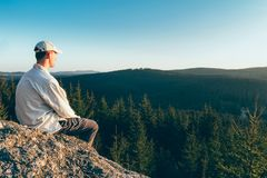 Young man hiker in white cap and shirt sit on rock from back looking to valley.  stock images