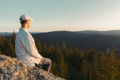 Young man hiker in white cap and shirt sit on rock from side looking to valley.  stock image