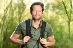 Young man hiking. Smiling happy portrait. Male hiker walking in forest Royalty Free Stock Photography