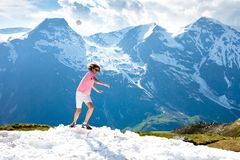 Young man hiking in Alps mountains. Austria. Teenager playing snow ball fight on snowy mountain peak on warm sunny spring day. Summer family vacation. Teen boy Stock Photos