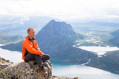 Young man hiking on Besseggen. Happy guy enjoy beautiful lake and good weather in Norway. Stock Images