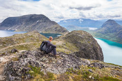 Young man hiking on Besseggen. Happy guy enjoy beautiful lake and good weather in Norway. Royalty Free Stock Photos