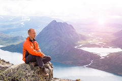 Young man hiking on Besseggen. Happy guy enjoy beautiful lake and good weather in Norway. Toning picture. Young man hiking on Besseggen. Happy man enjoy lake and Stock Photo