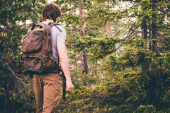 Young Man hiking in forest with backpack Travel Lifestyle Royalty Free Stock Images