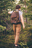 Young Man hiking in forest with backpack Travel Lifestyle Royalty Free Stock Image