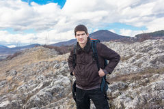 Young Man hiking in the Mountains. Portrait of young hiker with backpack Stock Photography