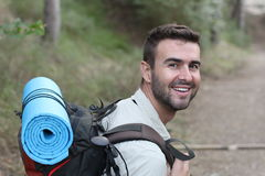 Young man hiking smiling happy portrait. Male hiker walking in forest.  Royalty Free Stock Images