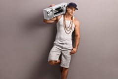 Young man in hip-hop clothes carrying a stereo Stock Photos