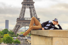 Young man hipster on the background of the Eiffel tower, France Royalty Free Stock Image