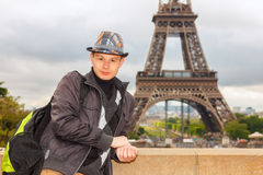 Young man hipster on the background of the Eiffel Tower, Paris. Young man hipster in a hat and vest on the background of the Eiffel Tower (La Tour Eiffel) in Royalty Free Stock Photos