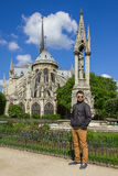 Young man hipster in a glasses near Cathedral of Notre Dame de P. Young man hipster in a glasses near The southern facade of Cathedral of Notre Dame de Paris at Royalty Free Stock Photos