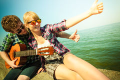 Young man hipster with guitar and woman. Royalty Free Stock Image