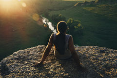 Young man hipster with long hair sitting at cliff edge and looking at sunset and nature, view from back Royalty Free Stock Photography