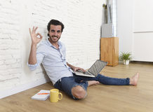 Young man in hipster modern casual style look sitting on living room home floor working on laptop Stock Image