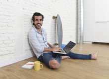 Young man in hipster modern casual style look sitting on living room home floor working on laptop Stock Photos