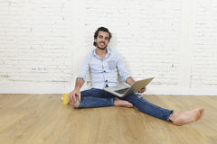 Young man in hipster modern casual style look sitting on living room home floor working on laptop Royalty Free Stock Photography