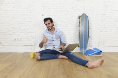 Young man in hipster modern casual style look sitting on living room home floor working on laptop Royalty Free Stock Image