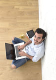Young man in hipster modern casual style look sitting on living room home floor working on laptop Stock Photo