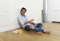 Young man in hipster modern casual style look sitting on living room home floor working on laptop Royalty Free Stock Photo