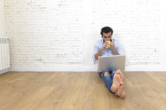 Young man in hipster modern casual style look sitting on living room home floor working on laptop Royalty Free Stock Photos