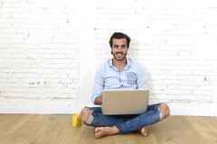 Young man in hipster modern casual style look sitting on living room home floor working on laptop Stock Images