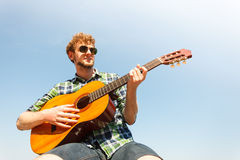 Young man hipster playing guitar. Royalty Free Stock Images